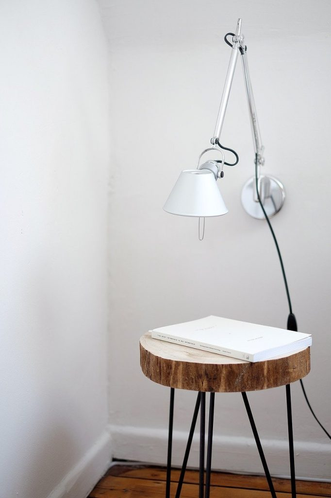 A natural wood side table compliments leaf print wallpaper