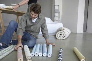 Man looking at rolls of wallpaper